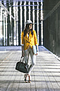 Spain,Catalunya, Barcelona, young modern businesswoman with yellow jacket on the move - EBSF000196