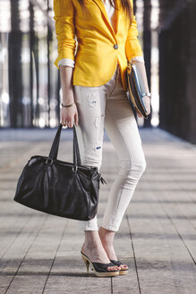 Spain,Catalunya, Barcelona, young modern businesswoman with yellow jacket on the move, partial view - EBSF000195