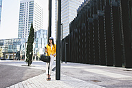 Spain,Catalunya, Barcelona, young modern woman with yellow jacket leaning against street lamp - EBSF000211