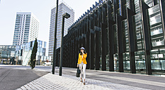 Spain,Catalunya, Barcelona, young modern woman with yellow jacket on the move - EBSF000202