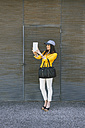 Spain,Catalunya, Barcelona, young modern woman with yellow jacket photographing herself - EBSF000209