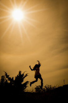 Silhouette of jumping woman in backlight - ABAF001327