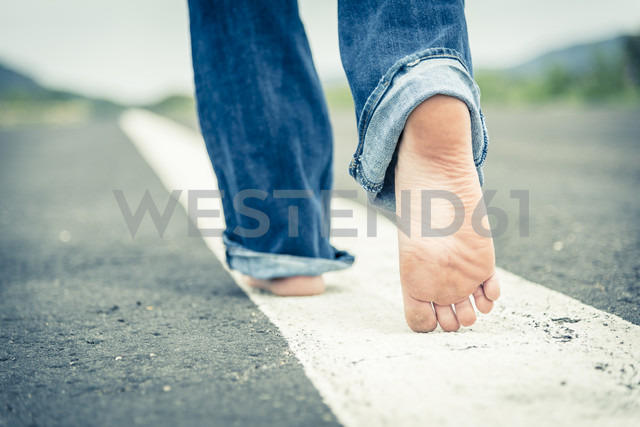 Young woman walking barefoot on centre line of empty street, partial view - ABAF001336