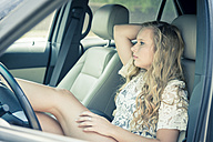 Young woman sitting in car watching something - ABAF001340