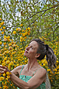 Mature woman at flowering bush looking up - AKF000380