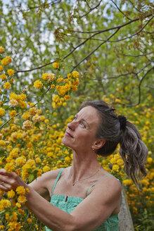 Mature woman at flowering bush looking up - AKF000380