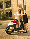Two young woman with road map and Vespa - FCF000179