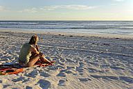 Australia, Western Australia, Lancelin, woman sitting on the beach looking at the sea - MIZ000466