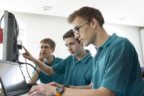Three electronic apprentices testing at workshop - SGF000653