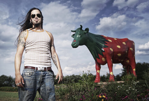 Portrait of a cool guy in front of a painted strawberry cow - IP000116