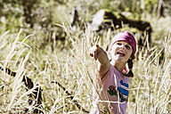 Girl in high grass pointing finger - HHF004816