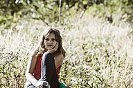 Girl sitting in meadow - HHF004795