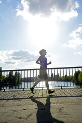 Young woman jogging over bridge at back light - BFRF000406