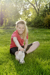 Young woman doing stretching exercise while sitting on meadow - BFRF000409