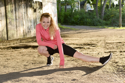 Young woman doing stretching exercise on sand - BFRF000414