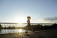 Young woman jogging over bridge at back light - BFRF000416