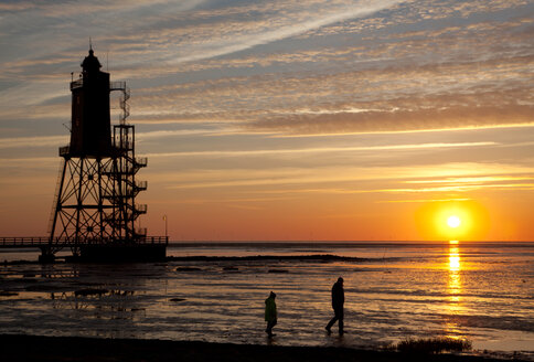 Germany, Lower Saxony, Dorum, lighthouse Obereversand and two walkers at sunset - OLE000018