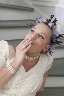 Portrait of smoking bride with curlers - ECF000615