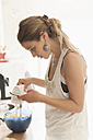 Young woman reading baking recipe at smartphone while mixing dough - TCF004008