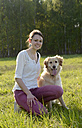 Young woman sitting with Golden Retriever on meadow - BFRF000425