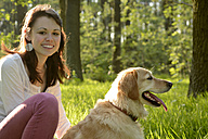 Portrait of young woman sitting with Golden Retriever on meadow - BFRF000432