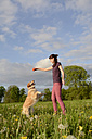 Young woman playing with Golden Retriever on meadow - BFRF000438