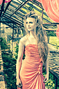 Young woman wearing evening dress standing in old greenhouse - FCF000201