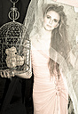 Young woman with teddy bear in bird cage wearing evening dress - FCF000203