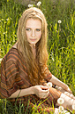 Portrait of young woman sitting on summer meadow - FCF000204