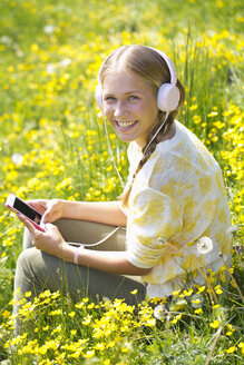 Portrait of smiling teenage girl with headphones hearing music on a flower meadow - WWF003306