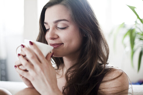 Portrait of young woman drinking coffee at home - FEXF000075