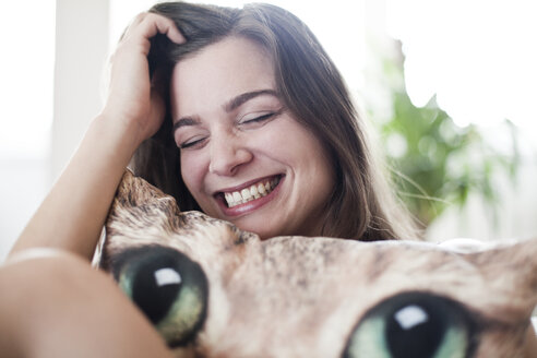 Portrait of laughing young woman with funny sofa cushion at home - FEXF000078