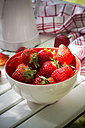 Bowl of strawberries, kitchen towel and jar on white wood - LVF001245