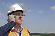 Germany, technician with safety helmet in front of wind turbines - SGF000681