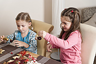 Two little girls tinkering Christmas decoration - ECF000635