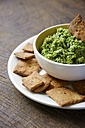 Bowl of dip made from peas, rocket salad, mint and soy yogurt with home-made crackers - HAWF000175