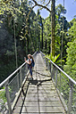 Australia, New South Wales, Dorrigo, girl standing on a suspension bridge in the rainforest of the Dorrigo National Park - SHF001330