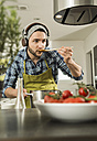 Young man with headphones cooking in kitchen at home - UUF000531
