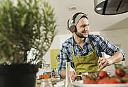 Young man with headphones cooking in kitchen at home - UUF000532