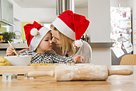 Mother and daughter wearing Santa hats baking in kitchen - UUF000539