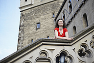 Germany, North Rhine-Westphalia, Cologne, woman leaning on railing of an old tower - RHF000336