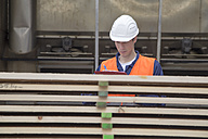 Young worker at carpentry of pallet production - SGF000691