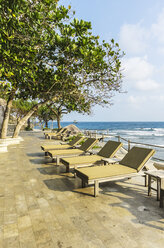 Indonesia, Riau Islands, Bintan, Nikoi Island, Sun loungers at hotel pool - THA000348