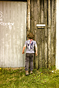 Little boy peeking through spy hole in garage - TKF000348