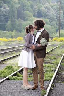 Kissing bridal couple standing between rails - ND000446