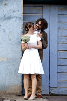Bridal couple standing in front of blue wooden door - ND000456