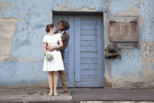 Bridal couple standing in front of blue wooden door - ND000457