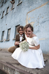 Bridal couple crouching in front of an old industrial building - ND000459