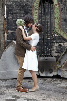 Bridal couple kissing in front of an old excavator shovel - ND000464