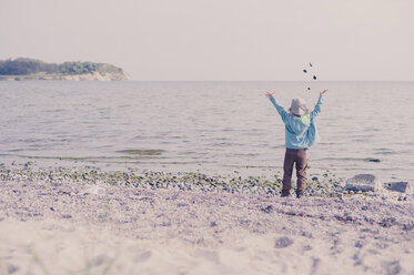 Germany, Mecklenburg-Western Pomerania, Ruegen, Boy on shingle beach throwing stones in the ocean - MJF001168